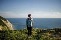 Visão traseira da mulher com mochila em pé na colina e olhando para a frente no mar — Fotografia de Stock