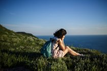 Brunette woman with backpack sitting on grass on hill over sea — Stock Photo