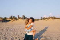 Mutter und Tochter umarmen sich am Strand, Fokus auf Vorder- — Stockfoto