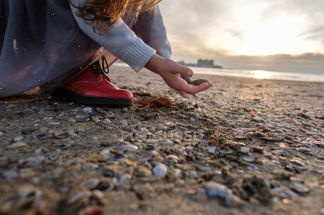 Cropped view of girl with stones at beach, selective focus — Stock Photo