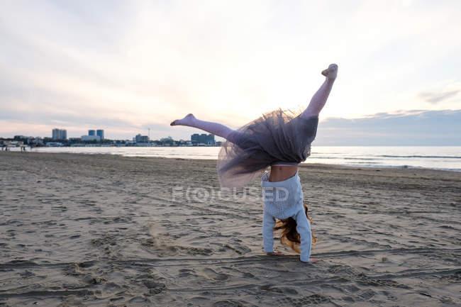 Девушка делает акробатическое колесо на пляже, избирательный фокус — стоковое фото