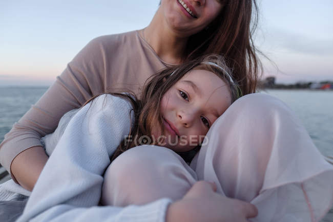 Daughter embracing mother against sea, focus on foreground — Stock Photo