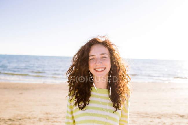 Rindo jovem com fones de ouvido ouvindo música na praia, foco seletivo — Fotografia de Stock