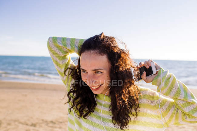 Laughing young woman with earphones listening music on beach, selective focus — Stock Photo