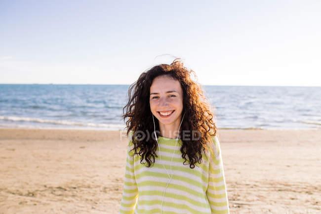 Сміючись молода жінка з навушники, прослуховування музики на пляжі, вибіркове фокус — стокове фото