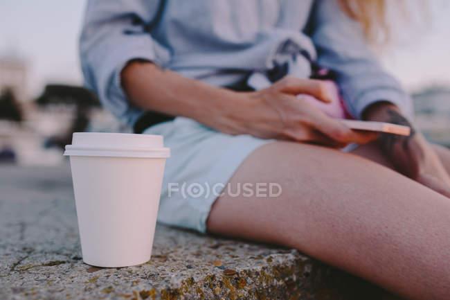 Tasse en plastique blanche de café près de la femme assise avec le téléphone intelligent — Photo de stock