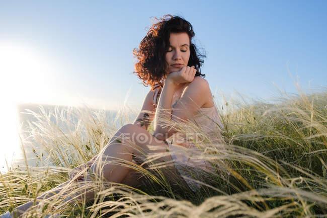 Jovem morena com tatuagem sentada na grama, foco em primeiro plano — Fotografia de Stock