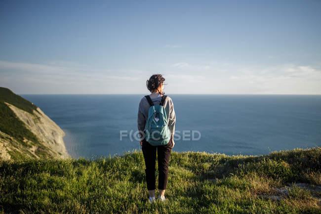 Vista posteriore della donna con zaino in piedi sulla collina e guardando avanti sul mare — Foto stock