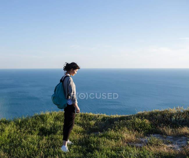 Jeune femme avec sac à dos debout sur la colline et regardant vers l'avant sur la mer — Photo de stock