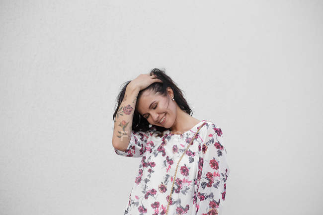 Brunette woman in floral dress with tattoo isolated on white background — Stock Photo