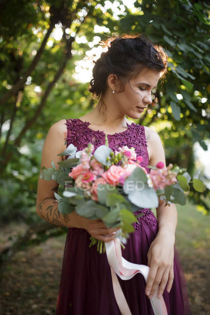 Young woman in purple summer dress posing with flowers bouquet — Stock Photo