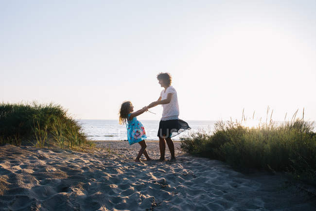 Mother and daughter having fun on beach, selective focus — Stock Photo