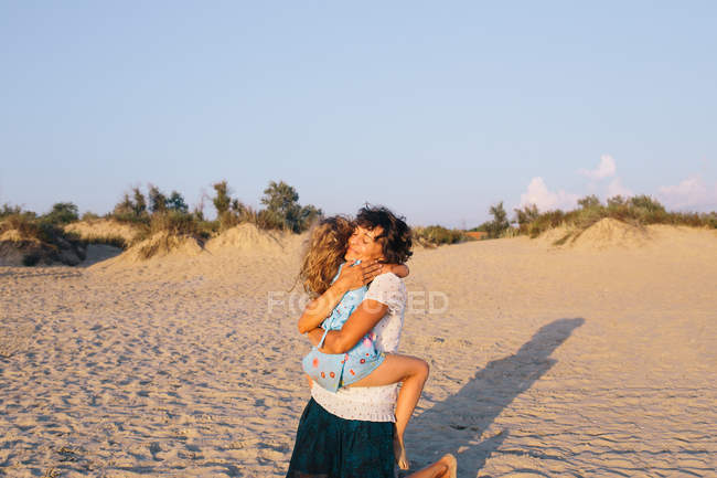 Mother and daughter hugging at beach, focus on foreground — Stock Photo