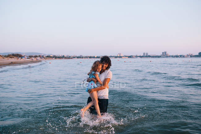Mother and daughter having fun on beach, focus on foreground — Stock Photo