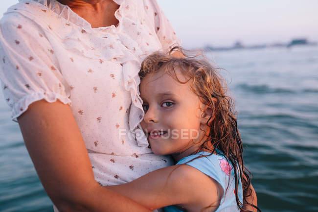 Recadrée vue de fille mignonne avec la mère étreindre — Photo de stock