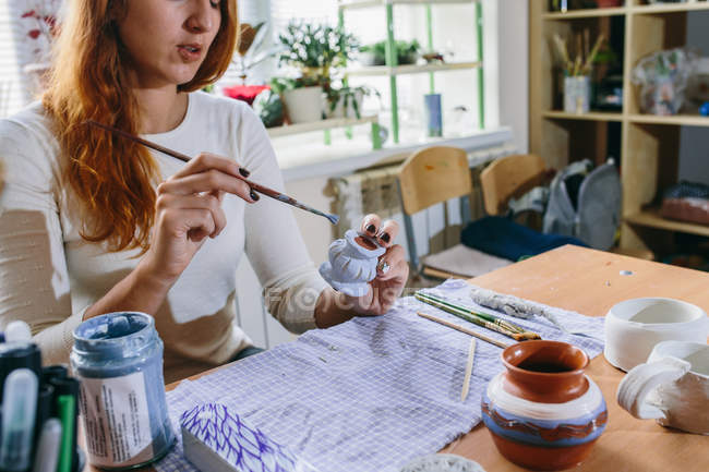 Cropped view of young woman drawing on small clay pot, selective focus — Stock Photo