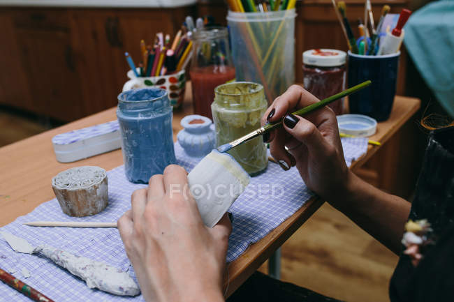 Cropped view of young woman pottery painting clay cup, working in pottery studio — Stock Photo