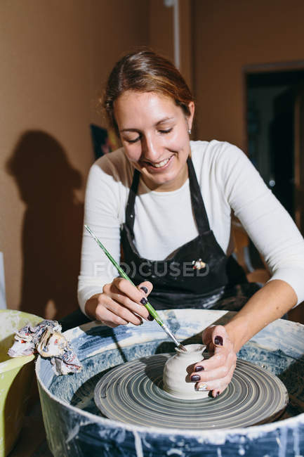 Young woman making clay pot on pottery wheel, selective focus — Stock Photo