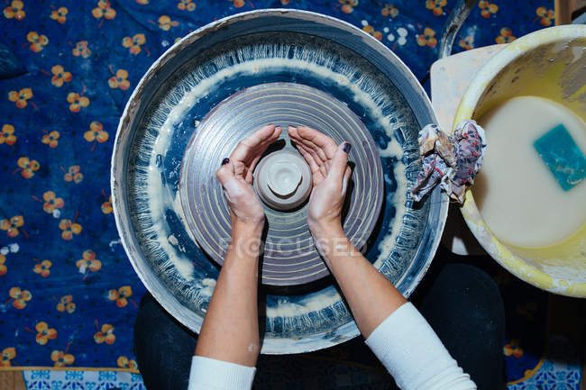 Elevated view of female hands in clay in potters wheel creating product — Stock Photo