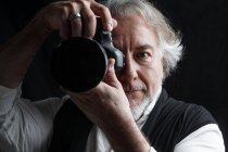 Professional mature photographer using photo camera and looking at camera isolated on black — Stock Photo