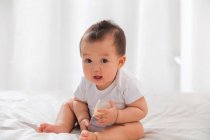 Lovely asian baby sitting on bed wity baby bottle and looking at camera — Stock Photo
