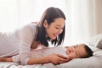 Felice giovane madre guardando adorabile bambino dormire sul letto — Foto stock