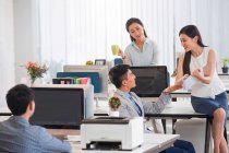 Professional young asian businessmen and businesswomen working with computers and discussing project in office — Stock Photo