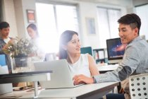 Giovane uomo d'affari sorridente guardando donna d'affari felice utilizzando il computer portatile sul posto di lavoro — Foto stock