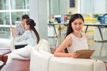 Beautiful young asian businesswoman holding clipboard and smiling at camera in office — Stock Photo