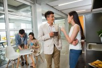 Felice giovane uomo d'affari asiatico e donna d'affari in possesso di tazze e parlando durante la pausa caffè in ufficio — Foto stock
