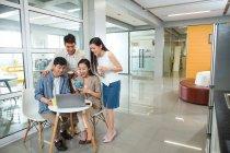 Felice giovani uomini d'affari asiatici e donne d'affari in possesso di tazze e utilizzando il computer portatile insieme in ufficio — Foto stock