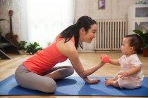 Vue latérale de la jeune mère exerçant avec haltère et regardant le bébé mignon s'asseyant sur le tapis de yoga à la maison — Photo de stock