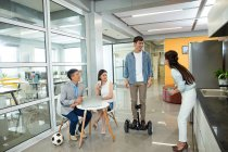 Happy young asian business people spending time with gyroscooter and soccer ball in office — Stock Photo