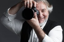 Professional male mature photographer working with photo camera and smiling at camera isolated on grey — Stock Photo