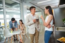 Giovani colleghi di lavoro sorridenti che tengono le tazze e parlano durante la pausa caffè in ufficio — Foto stock