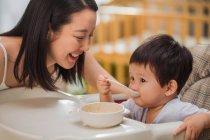 Щаслива молода мати дивиться на чарівні маленька дитина їсть вдома — стокове фото