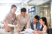 Profesional joven asiático negocio equipo trabajando con papers y discutir nuevo proyecto en oficina - foto de stock