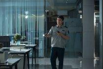 Junge asiatische Sicherheitsmann mit Taschenlampe und Walkie-Talkie im Büro in der Nacht — Stockfoto