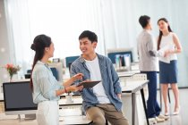 Smiling young asian business colleagues using digital tablet and discussing work in office — Stock Photo