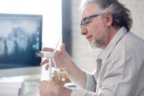 Боковой вид серьезного профессионального зрелого архитектора в очках с моделью ветрового стекла на рабочем месте — стоковое фото