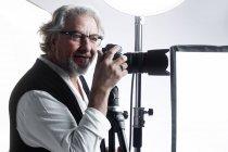 Profissional sorrindo fotógrafo maduro trabalhando com câmera de fotos e olhando para longe em estúdio — Fotografia de Stock