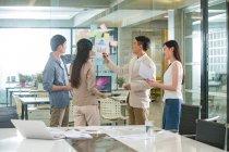 Giovani colleghi di lavoro asiatici che lavorano con documenti in ufficio — Foto stock