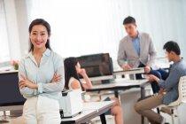 Confiada mujer de negocios asiática con brazos cruzados sonriendo a la cámara mientras sus colegas trabajan detrás en la oficina - foto de stock