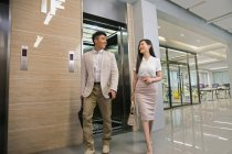 Молодой азиатский бизнесмен и деловая женщина улыбаются друг другу, выходя из лифта в офисе — стоковое фото