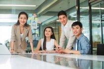 Professionisti giovani uomini d'affari asiatici e donne d'affari sorridenti alla macchina fotografica mentre lavorano insieme in ufficio — Foto stock