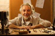 Professionnel mature mâle créateur de bijoux assis sur le lieu de travail et souriant à la caméra — Photo de stock
