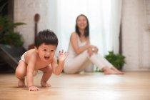 Очаровательный взволнованный азиатский ребенок в подгузнике, приседающий на полу, в то время как счастливая мать сидит позади, избирательный фокус — стоковое фото