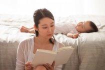 Focalizzato giovane donna asiatica lettura libro mentre bambino dormire sul letto dietro — Foto stock