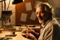 Профессиональный зрелый дизайнер ювелирных изделий, работающий с инструментами и улыбающийся в мастерской — стоковое фото