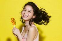 Schöne, glückliche junge Frau hält bunten Lutscher und lächelt in die Kamera auf gelb — Stockfoto